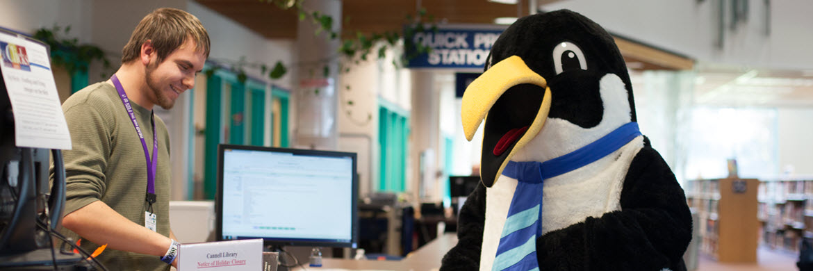 Oswald the penguin mascot in front of Check Out desk with smiling young man behind the counter