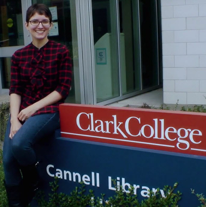 smiling woman sits on Cannell Library sign near the library's front door